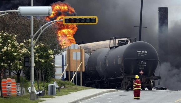 533750-a-firefighter-walks-past-a-burning-train-wagon-at-lac-megantic