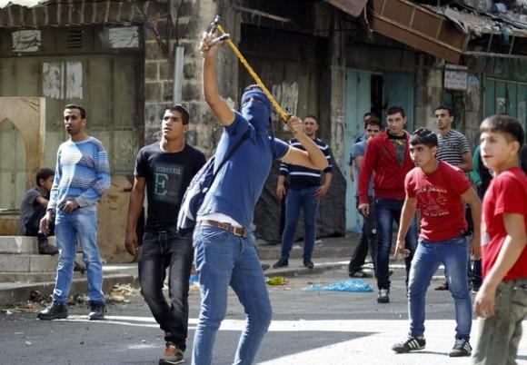 Un Palestinien utilise un lance-pierre lors d'affrontements avec les forces de sécurité israéliennes dans la ville d'Hébron en Cisjordanie.