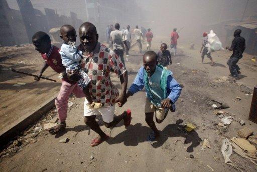 Un homme Kényan fuit  avec ses enfants loin de la violence post-électorale dans le bidonville de Mathare à Nairobi, au Kenya, le 1er Janvier 2008.