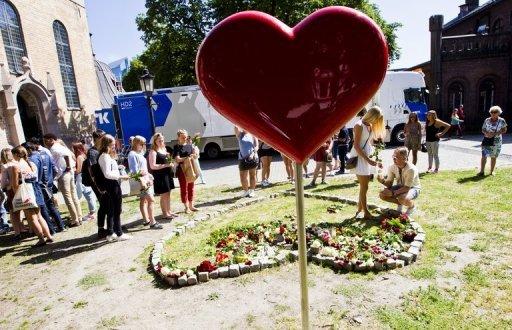 Les gens déposent des fleurs devant la cathédrale d'Oslo, après un service commémoratif pour le deuxième anniversaire du massacre d'Anders Breivik le 22 Juillet 2013.