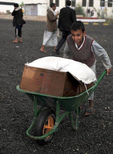 Un garçon déplacées pousse un terrier de roue chargée de l'aide humanitaire dans la capitale Sanaa, le 2 Août 2012.
