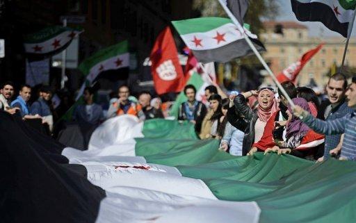 Manifestants brandissent des drapeaux de la Coalition nationale syrienne comme ils se mobilisent contre le président syrien Bachar al-Assad dans le centre de Rome, le 13 Avril 2013.