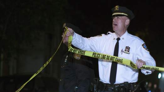 A NYPD officer holds police barrier tape as officers guard the scene of a stabbing incident at a Brooklyn residence, in New York