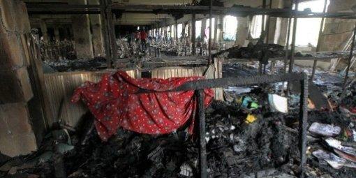 Les pompiers se tiennent près d'un feu comme ils essaient de le contrôler à l'intérieur d'une usine de confection au Bangladesh
