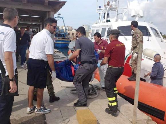 Les secouristes récupérent un corps à partir d'un bateau dans le port de Lampedusa, en Italie.