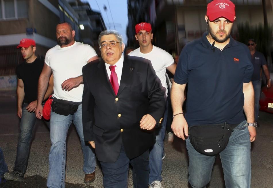 Des policiers armés ont conduit Nikolaos Mihaloliakos loin du palais de justice, menottes aux poignets.