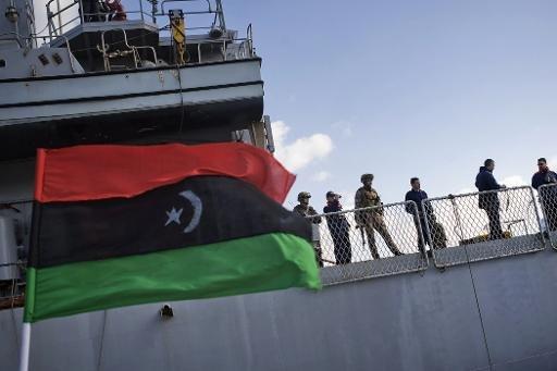 fichier image montre un vieux drapeau national libyen flottant à côté du navire de guerre italien dans le port de Benghazi en Libye le 7 Mars 2011