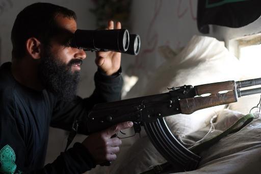 Un combattant de l'opposition utilise des jumelles pour observer le mouvement des forces du régime alors qu'il occupe un poste dans le cheikh al-Said quartier d'Alep, le 3 Octobre 2013
