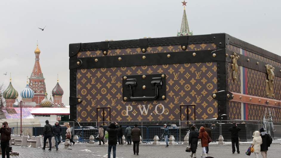 People walk past a Louis Vuitton pavilion which is in the shape of a giant suitcase in Moscow